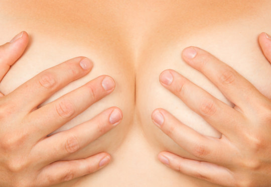 Upper part of female body, hands covering breasts